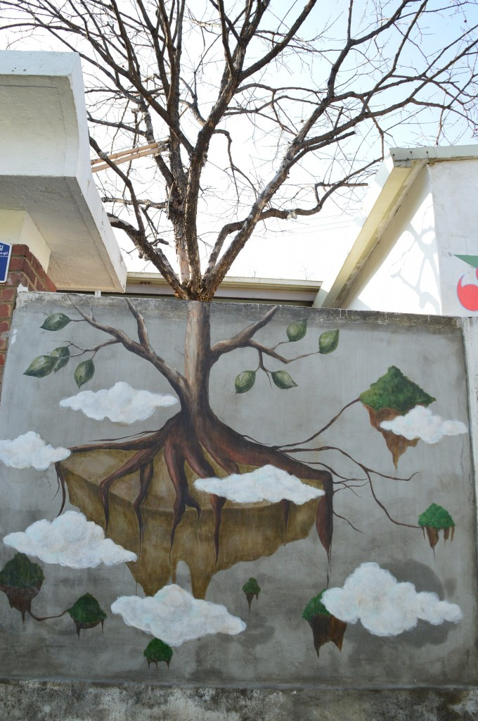 담 너머로 보이는 나무와 이어지는 모양의 나무벽화가 그려진 담