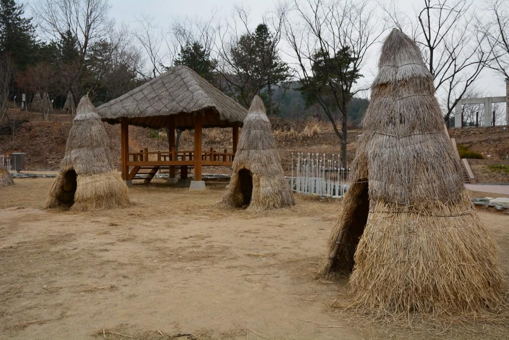 오두막 앞에 짚으로 만들어 놓은 집들