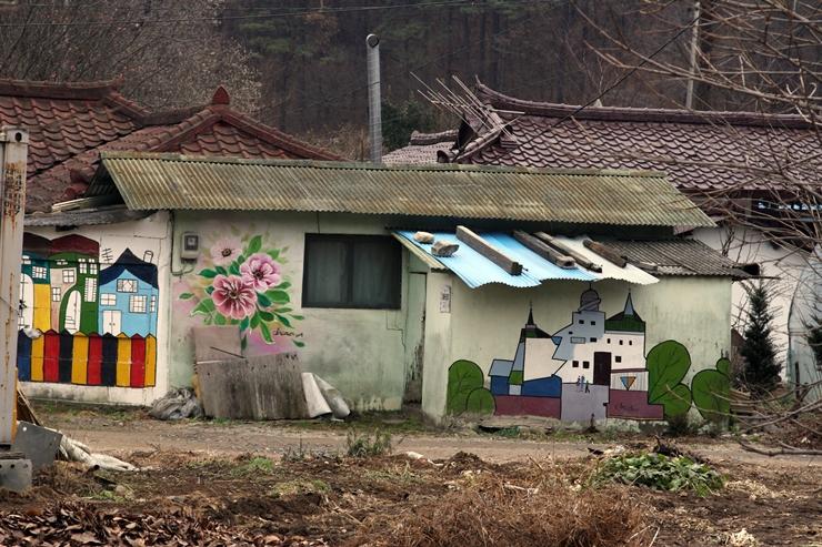 낡은 집 앞에 그려진 꽃과 집 벽화