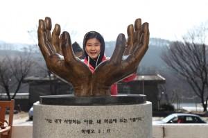 두개의 손으로 만들어진 조형물 가운데 서있는 아이