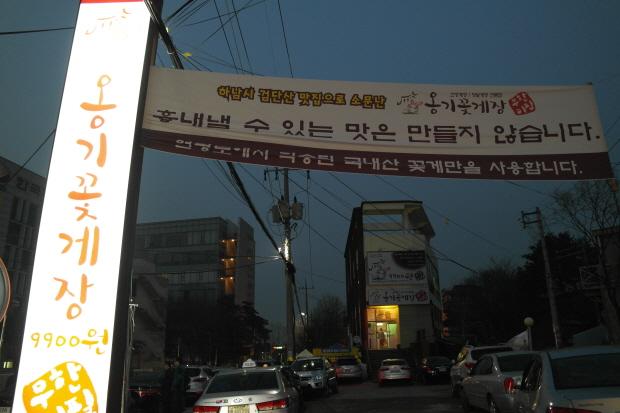 현수막이 걸려 있는 옹기꽃게장 음식점의 입구 모습