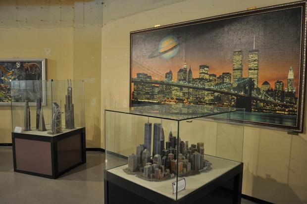 맨해튼의 마천루 작품과 그 뒤에 걸려 있는 커다란 맨해튼의 사진 퍼즐