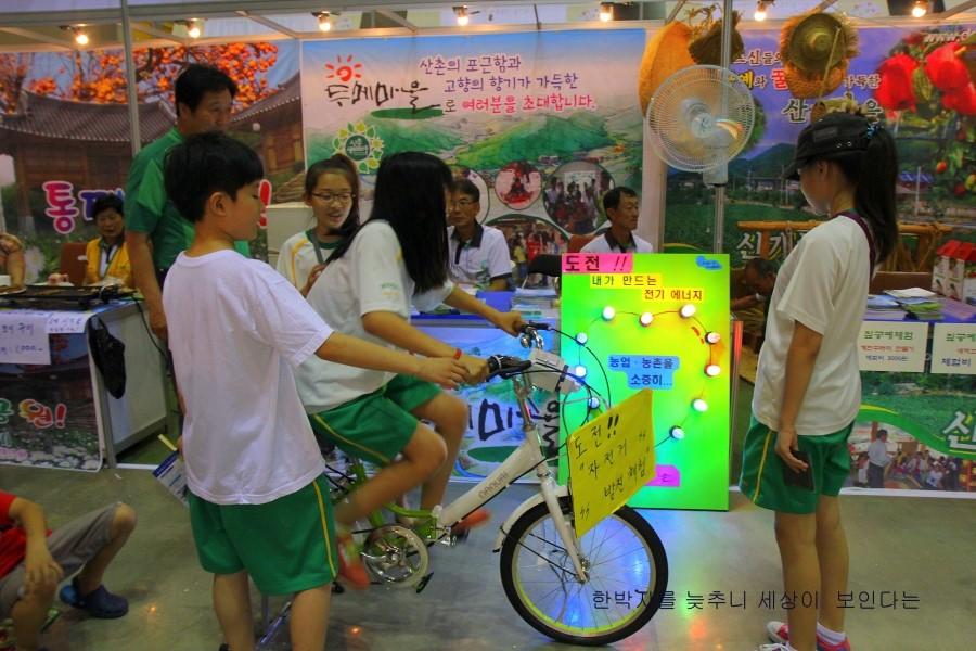 자전거 페달을 밟아 그 동력으로 전구에 불을 밝히는 행사에 참여하는 아이들