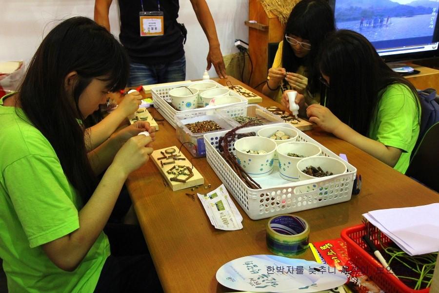 나무 판위를 여러가지 재료들로 장식하고 있는 아이들의 모습