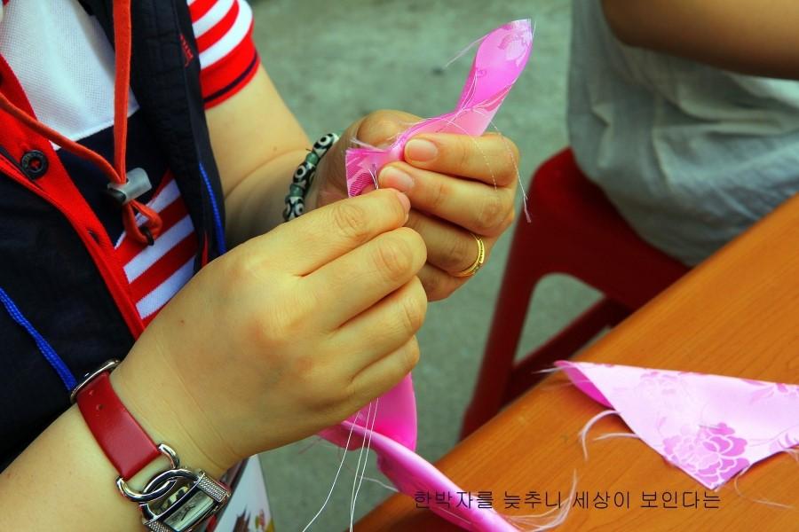 분홍색 천에 바느질을 하는 손