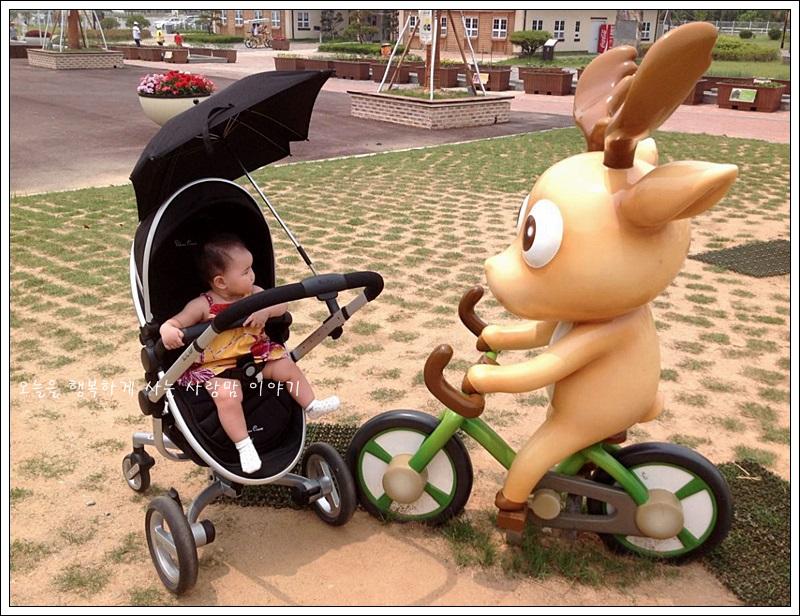 유모차를 탄 아기와 자전거를 타고 있는 모형사슴 인형의 모습