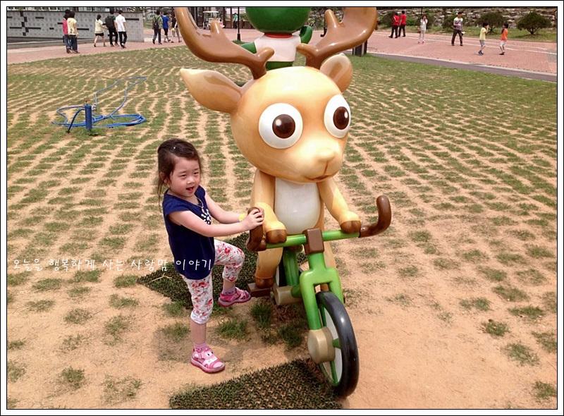 모형 사슴 인형옆에서 포즈를 취하고 있는 아이의 모습