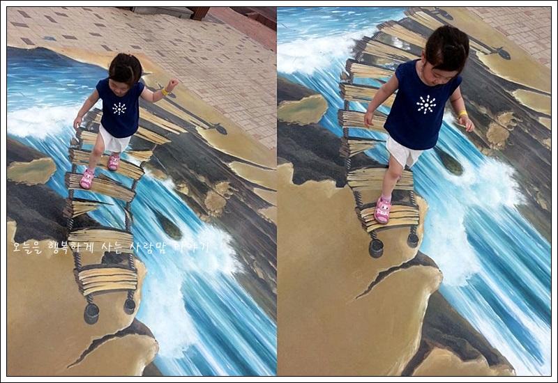 바닥에 그려진 낭떠러지에 나 있는 다리 모양의 그림 위를 걷고 있는 아이의 모습
