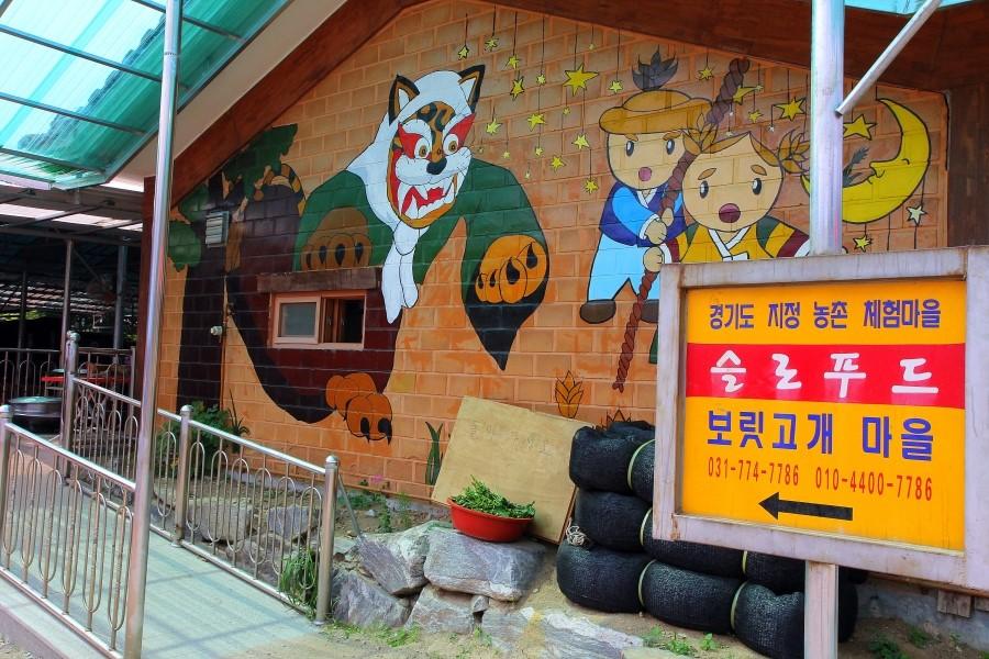 사람의 변장한 호랑이와 남매의 그림이 그려져 있는 벽면 앞에 세워져 있는 보릿고개마을의 간판 모습