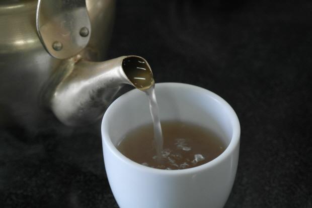 뜨거운 약수를 컵에 따르는 모습