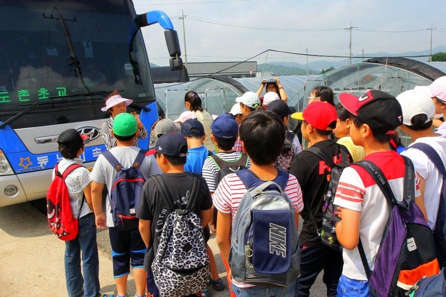 버스 앞에서 농정교육을 받고 있는 아이들의 모습