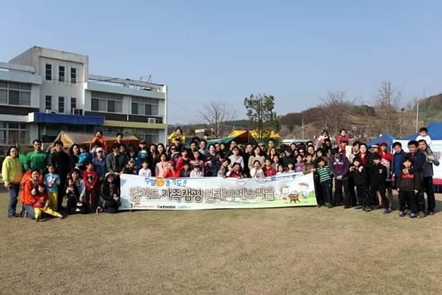 경기도 가족캠핑 릴레이페스티발이라 적힌 현수막 뒤에서 단체사진을 찍는 모습