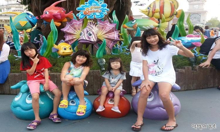 물고기 인형 앞에서 사진을 찍고 있는 아이들의 모습
