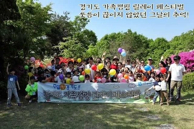 경기도 가족캠핑 릴레이 페스티발이라고 적힌 현수막 과 사진을 찍는 가족의 모습