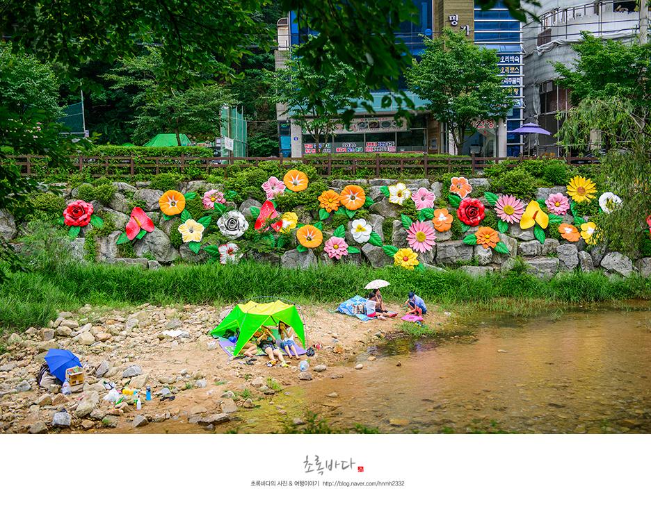 꽃 조형물이 붙어 있는 돌담과 그 앞에서 쉬고 있는 사람들의 모습