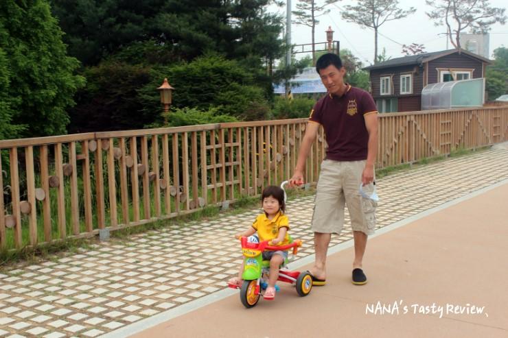 딸의 자전거를 끌어주는 아빠의 모습