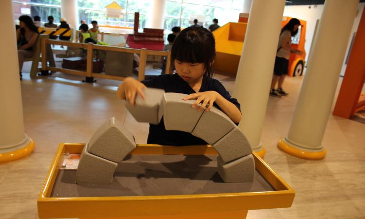 건축작업장에서 모형 아치구조를 만들고 있는 아이의 모습