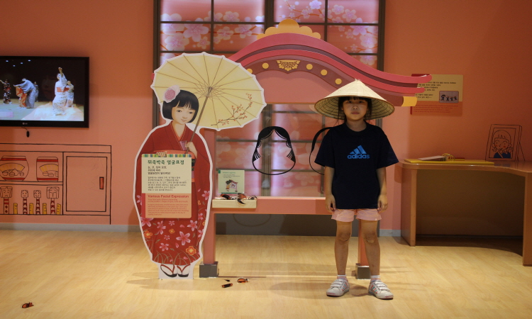 다른나라의 문화나 전통의상을 배울 수 있는 코너에서 삿갓을 쓰고 포즈를 취하고 있는 모습