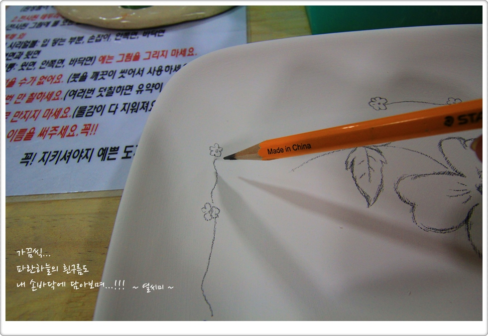 하얀 도자기 위에 연필로 그림을 그리고 있는 모습