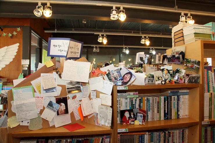 책장 위의 공간에 붙어 있는 수많은 엽서 및 사진의 모습