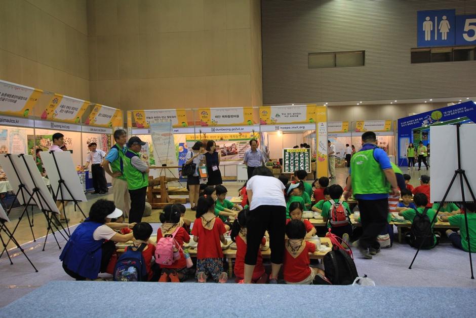 옹기 종기 모여 앉아 무언가 체험을 하고 있는 아이들의 모습