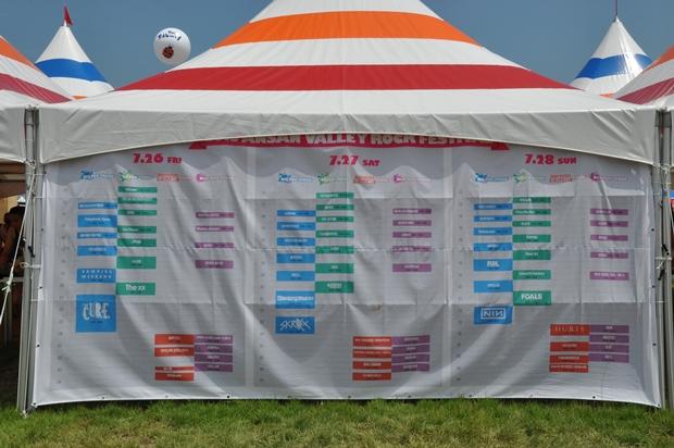 천막에 걸려 있는 행사일정과 공연이 열리는 무대 위치 현수막