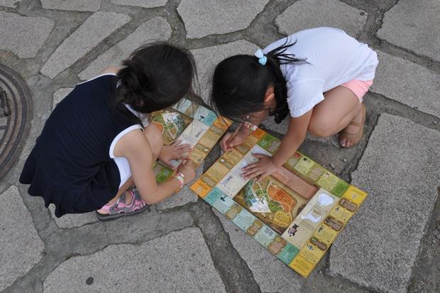 땅바닥에서 무언가 쓰고 있는 아이들의 모습