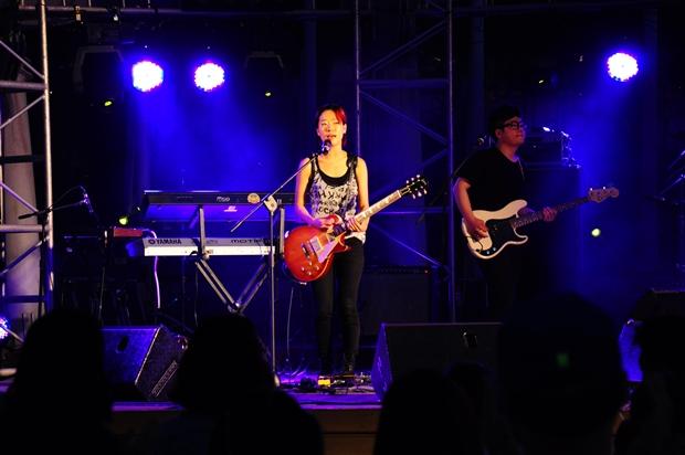 기타를 들고 민소매 티를 입은 무대위의 여성 보컬의 모습