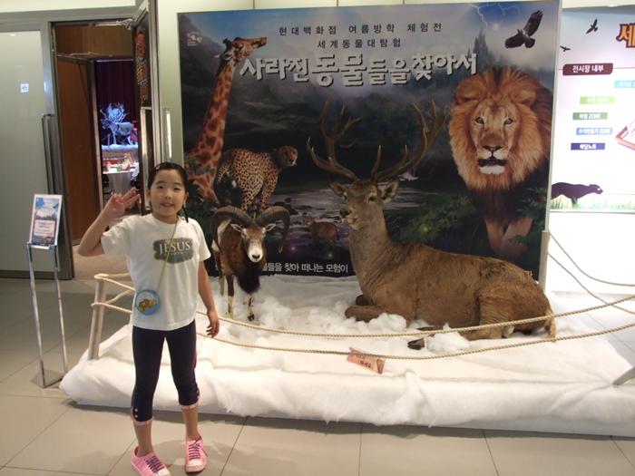 동물들의 모형 앞에서 포즈를 취하는 아이