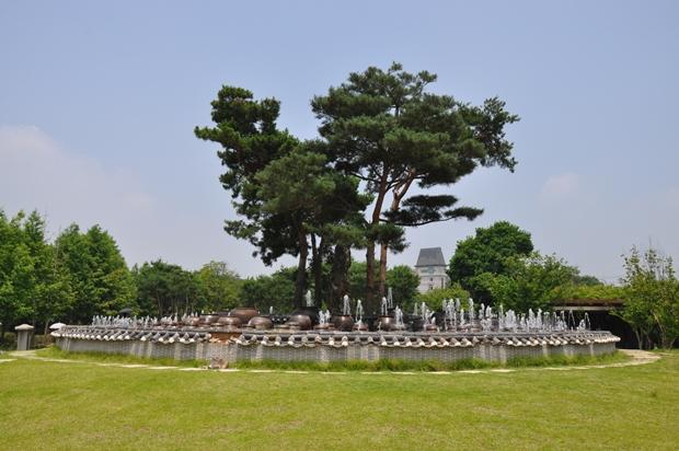 옹기위로 솟아 오르는 물줄기로 둘러 싸여 있는 거대한 나무의 모습