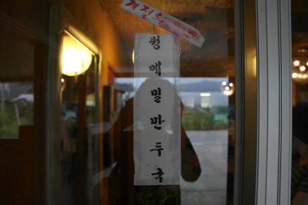 유리에 붙여논 꿩메밀 만두국 메뉴