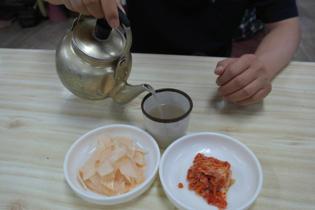 컵에 따뜻한 메밀국물을 따르고있다.