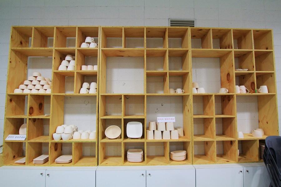 진열장에 가지런히 올려져 있는 그릇 및 컵들