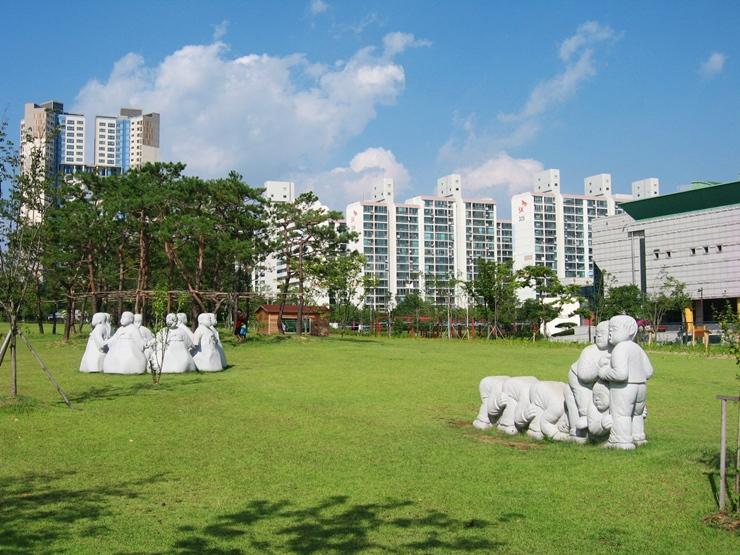 푸른하늘 아래 둘러앉아 놀고있는 모습의 조각상들