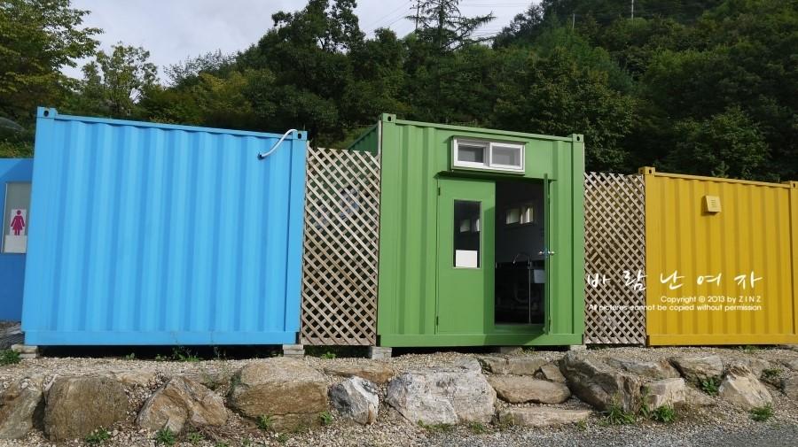 하늘색, 초록색, 노란색 컨테이너로 된 화장실 샤워실