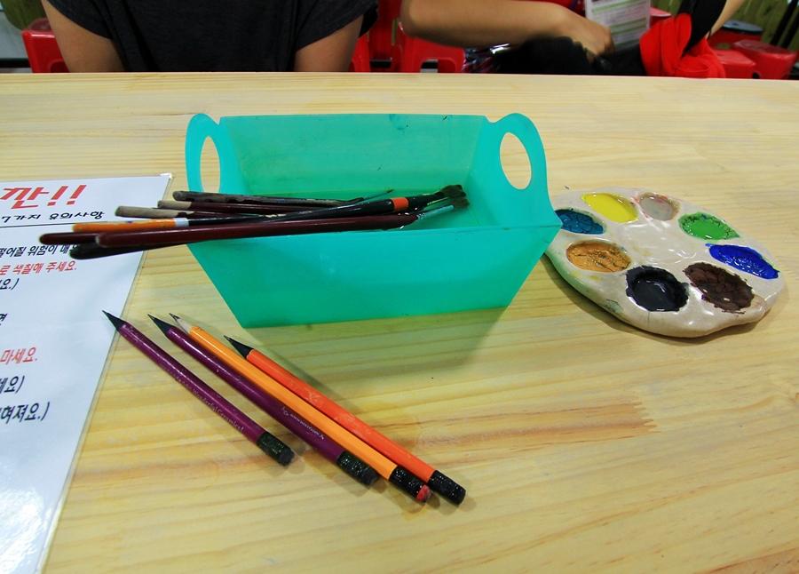 책상에 올려져 있는 붓 물감 팔렛트 4B연필 물통