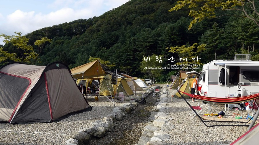 작은 냇가 양 옆으로 텐트가 설치되어 있다.