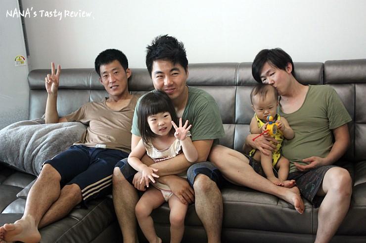 국방색 나시를 입은 남성들과 아이들이 소파에 앉아 있는 모습