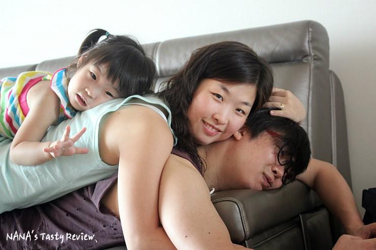 쇼파에 누워 있는 남녀와 그 위에 누운 여자아이