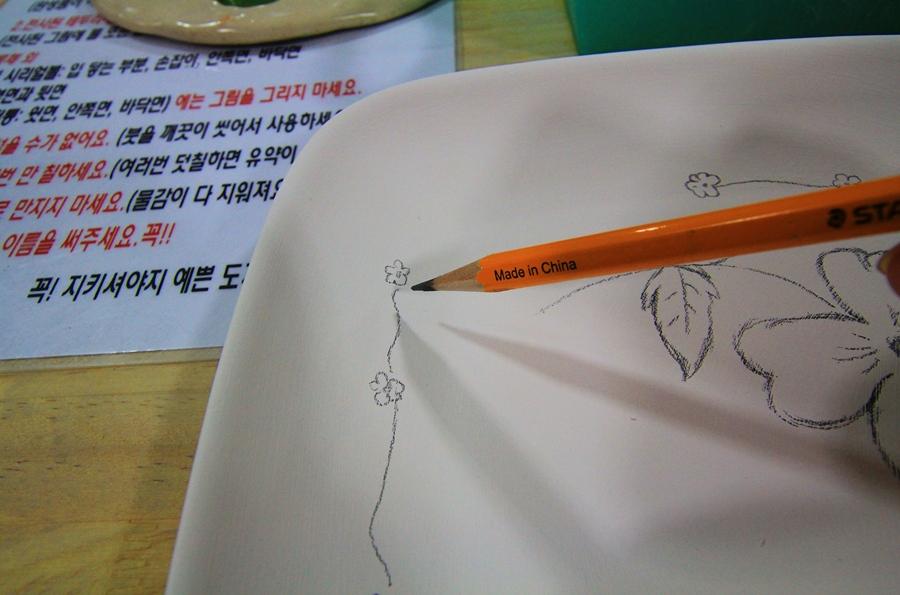 연필로 도자기 위에 스케치 하는 모습