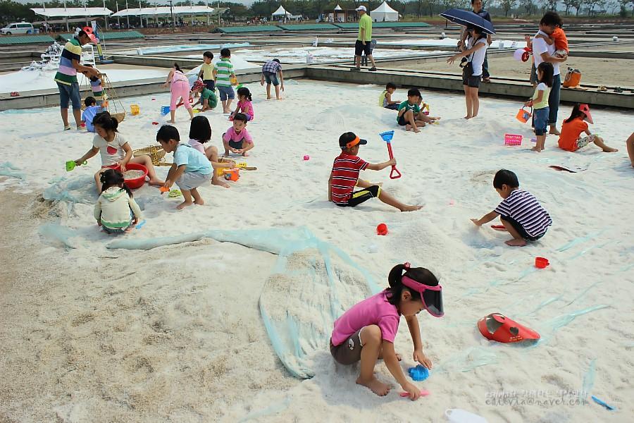 모래에서 도구들을 사용하여 놀고있는 아이들