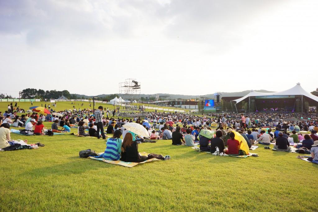 잔디밭에서 공연을 기다리는 관객들의 모습