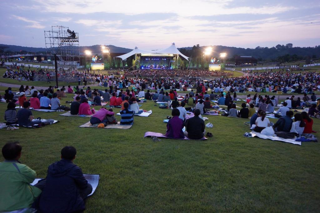 돗자리에 앉아 공연을 관람하는 사람들의 모습