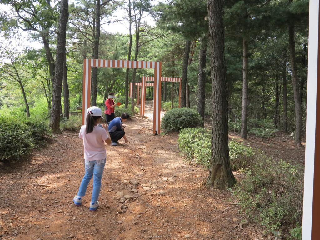 '다니엘 뷔렌'의 [숲을 지나서] 숲에 줄무늬 모양의 문이  세워져있다.