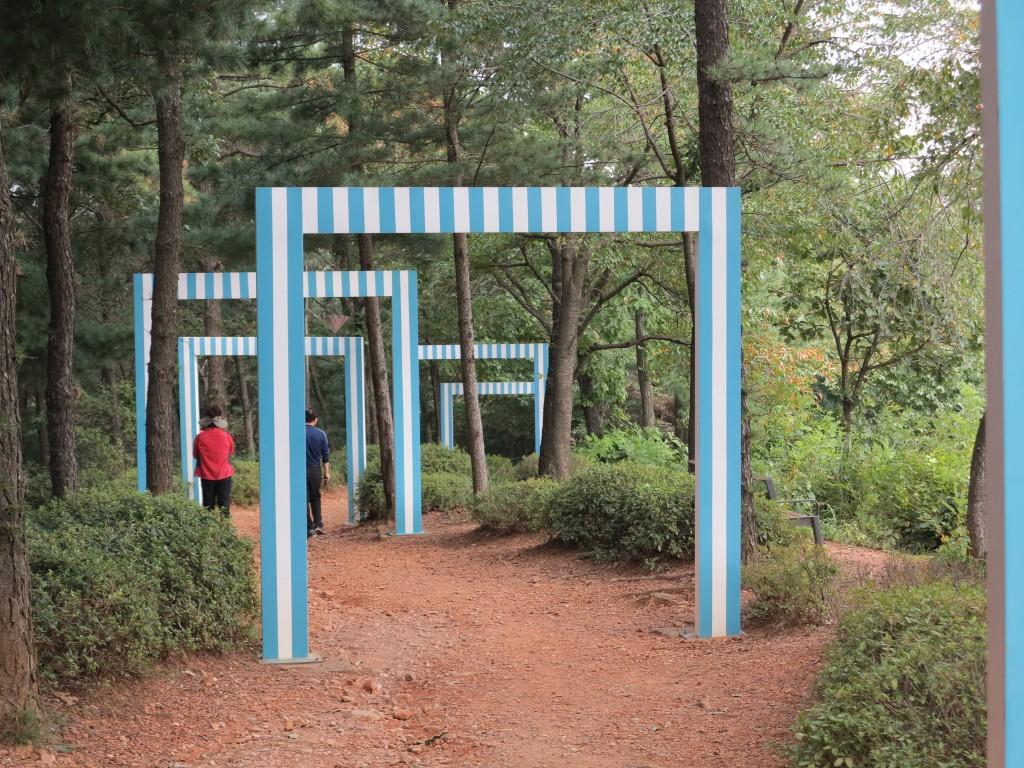 파란색 줄무니모양의 문이 숲길에 설치되어 있다.
