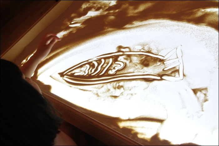 모래 위에 그려진 커다란 물고기 그림