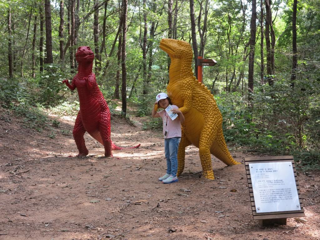 형형색색의 공룡조각 앞에서 사진을 찍는 아이