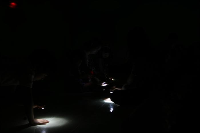 어두운 조명아래서 손전등을 비추는 아이들