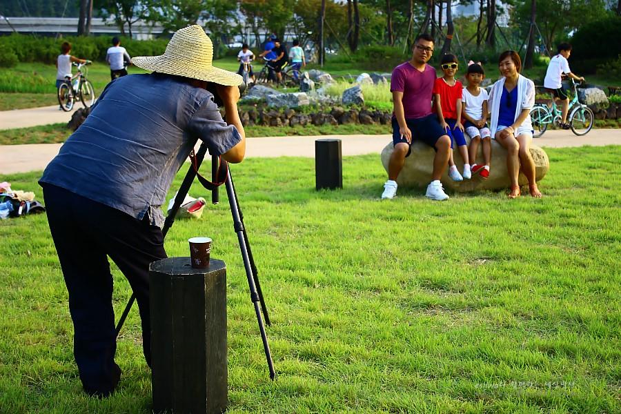 잔디밭에서 가족사진을 찍어주는 아저씨