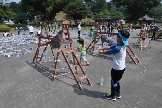 아이들이 모형 거중기를 이용하여 무거운 것을 끌어 올리는 체험하는 모습